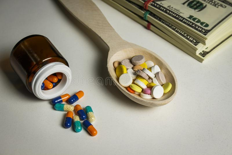 Vele gekleurde tabletten in een houten lepel en een kruik van capsules op een lijst stock afbeeldingen