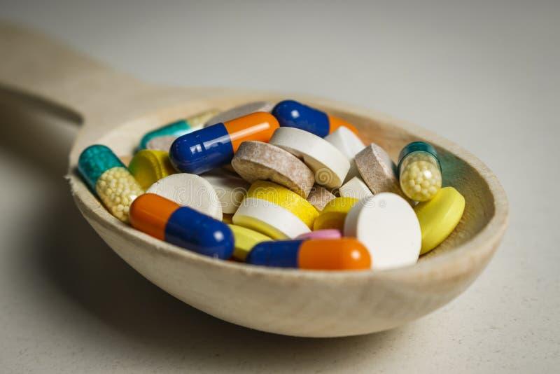 Vele gekleurde tabletten in een houten lepel op een lijst stock afbeeldingen
