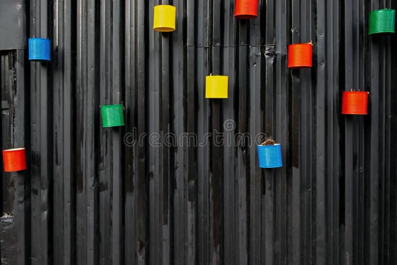 Vele geschilderde kleurrijke lege die blikken als bloempotten opnieuw worden gebruikt, opgezet aan de zwarte metaalmuur stock foto