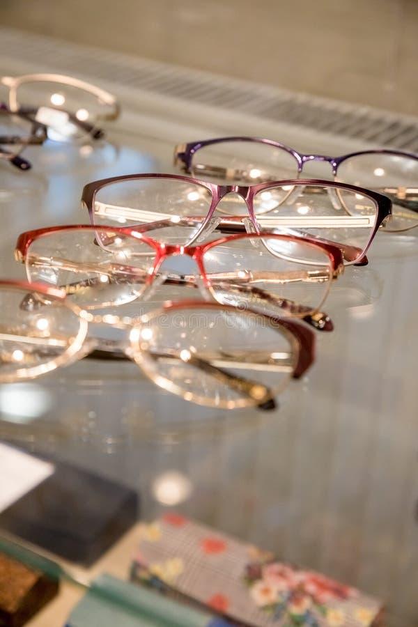 Vele glazenrijen bij optische detailhandel Rijke assortimentskeus van verschillende eyewear kaders op de vertoning van de oogglaz royalty-vrije stock foto