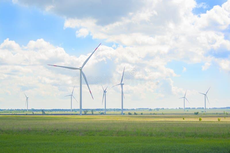 Vele grote en hoge windmolens bij zonnige dag op het groene gebied Alternatieve energiegenerators Windmolens bij zonsopgang Ecolo stock foto's