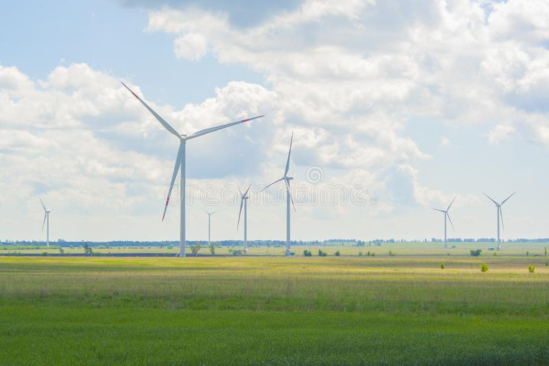 Vele grote en hoge windmolens bij zonnige dag op het groene gebied Alternatieve energiegenerators Windmolens bij zonsopgang Ecolo stock foto