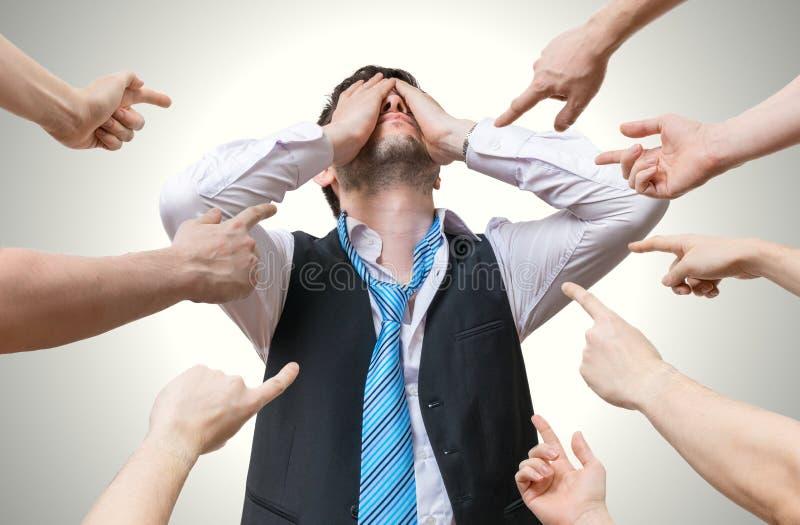 Vele handen die op de teleurgestelde mens richten en beschuldigen hem stock fotografie