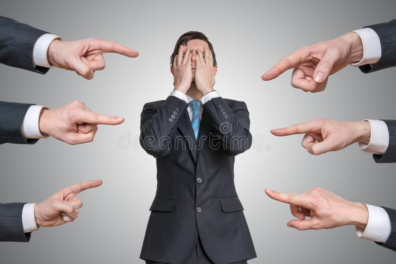 Vele handen richten op de schuldige mens en beschuldigen hem stock foto's