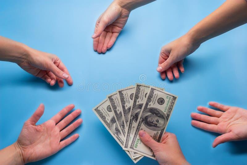 vele handenbereik voor geld stock afbeelding