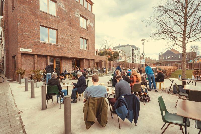 Vele jonge en bejaarde mensen die bij modern openluchtrestaurant dichtbij stadspark ontspannen stock foto's