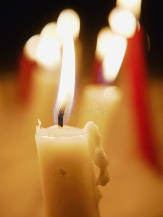 Vele kaarsen die sneeuw het branden plakken stock afbeelding