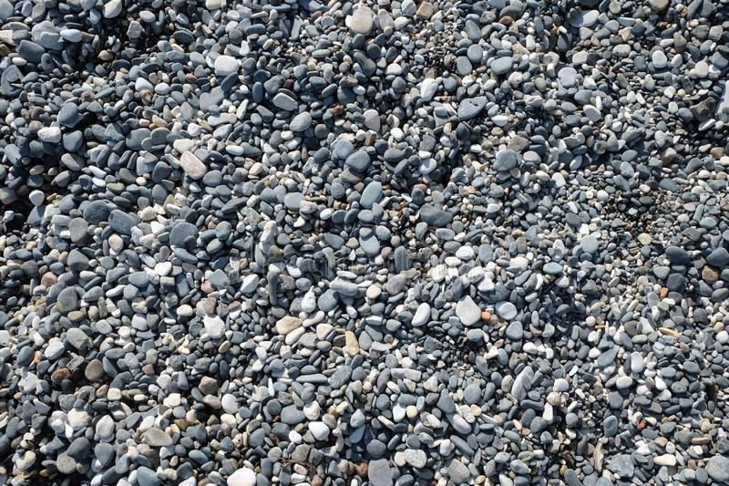 Vele kleine vlotte stenen op het overzeese strand op de zonnige close-up van de dag hoogste mening royalty-vrije stock fotografie