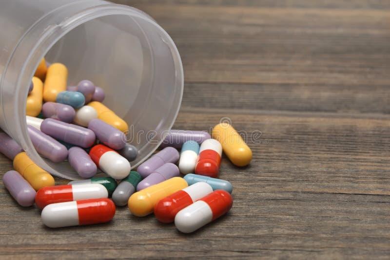 Vele Kleurrijke die Pillen en Capsules op Houten Achtergrond worden gelaten vallen royalty-vrije stock foto's