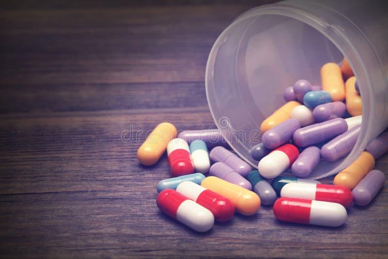 Vele Kleurrijke die Pillen en Capsules op Houten Achtergrond worden gelaten vallen royalty-vrije stock fotografie