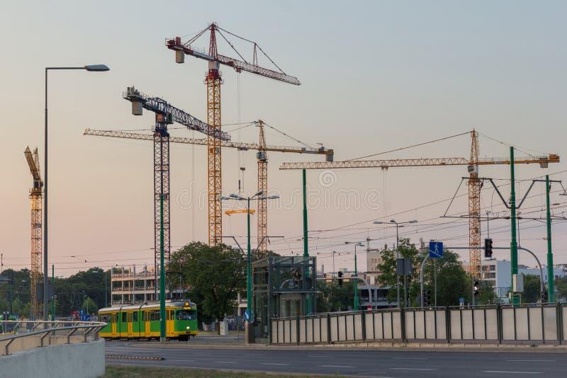 Vele kranen op de horizon en een voorbijgaande tram royalty-vrije stock foto's