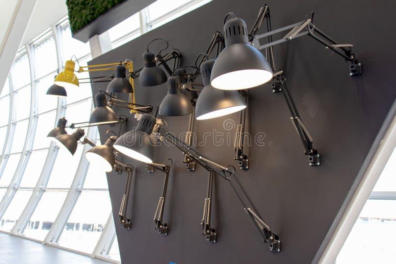 Vele lampen van zwarte en gele kleuren, installatie op zwarte muur voor een venster stock foto