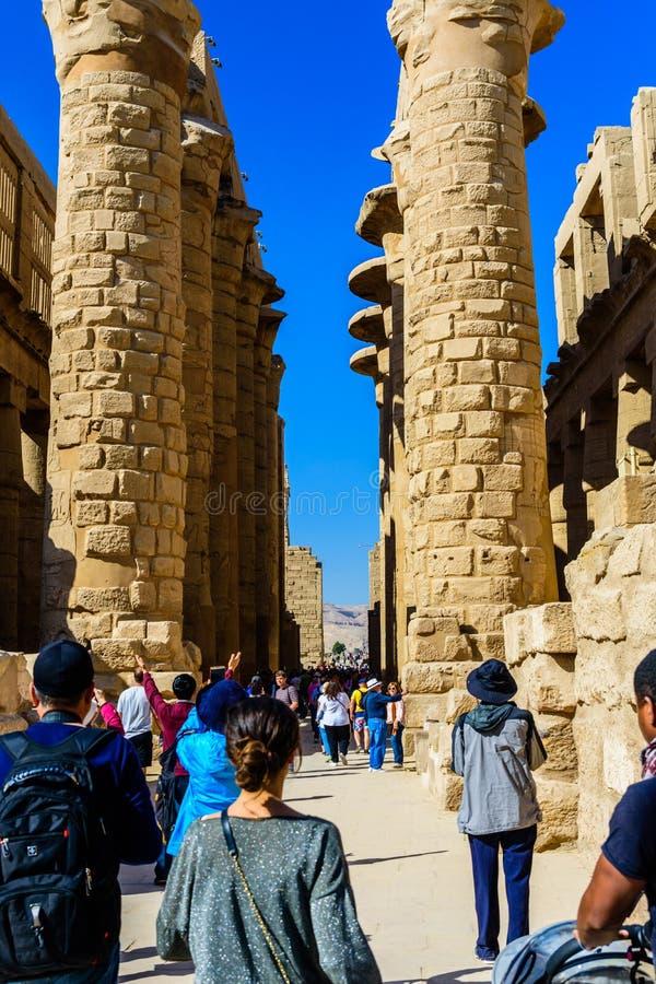 Vele mensen in de grote hypostyle zaal van de Karnak-tempel stock fotografie