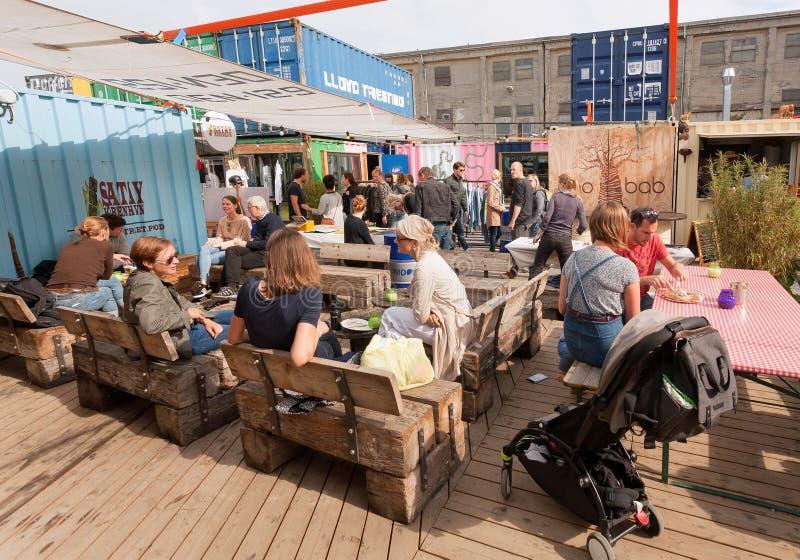 Vele mensen die abd het eten spreken samen bij snel voedselhof van straatmarkt met dranken en maaltijd royalty-vrije stock fotografie