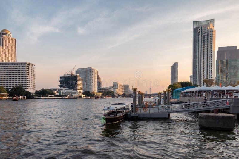 Vele mensen die door boot bij Chao Phraya-rivieroever reizen stock foto's