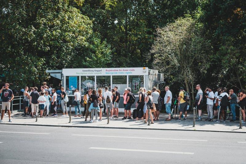 Vele mensen die zich in rij op straat bij toeristische attractie Duitse Reichstag op de zomerdag bevinden in Berlijn, Duitsland royalty-vrije stock foto's