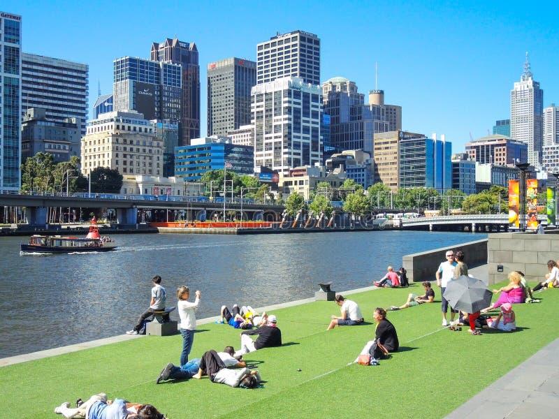 Vele mensen ontspannen in Groen gras openbaar park dichtbij Yarra-Rivier met de mening van de Wolkenkrabber van Melbourne stock fotografie