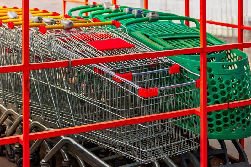 Vele metaalboodschappenwagentjes op een parkeerterrein dichtbij supermarkt in openlucht Het winkelen kwestiesconcept stock fotografie