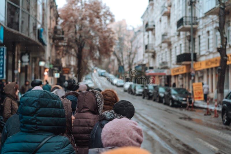 Vele niet ge?dentificeerde mensen wachten op stadsvervoer bij de bushalte stock afbeelding