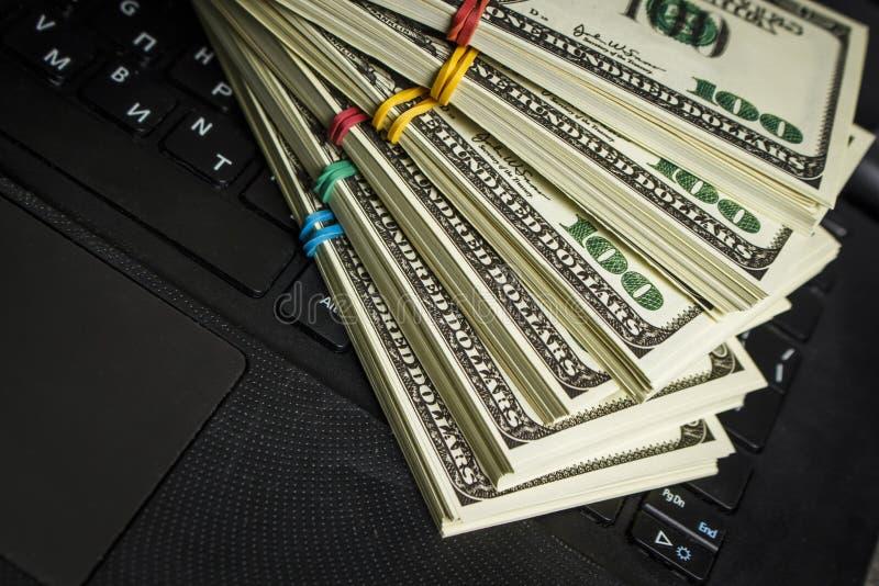 Vele pakken dollars op laptop stock afbeeldingen