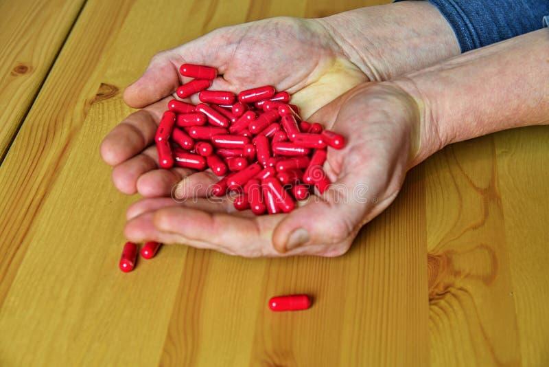 Vele pillen in de handen van een Oudste Pijnlijke oude dag Het geven voor de gezondheid van de bejaarden stock afbeelding
