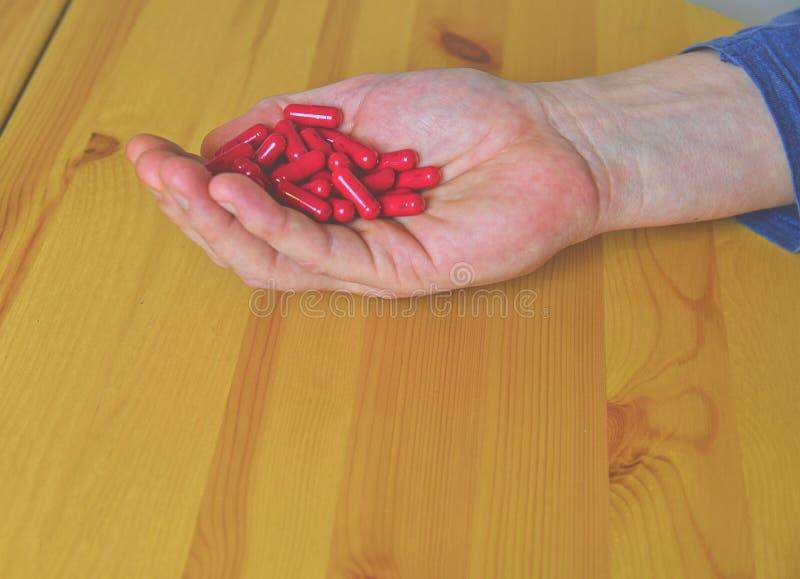 Vele pillen in een palm Pijnlijke oude dag Het geven voor de gezondheid van de bejaarden stock foto