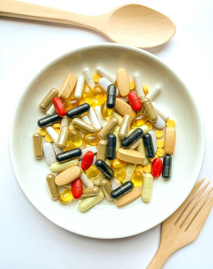 Vele pillen op een witte plaat stock afbeeldingen