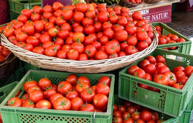 Vele Rijpe Rode Ronde Tomaten in Mand en Dozen, op verkoop in de Zomer royalty-vrije stock foto