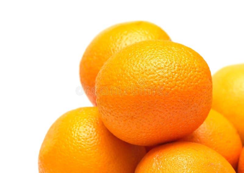 Vele rijpe sinaasappelenclose-up die op wit wordt geïsoleerd stock afbeeldingen