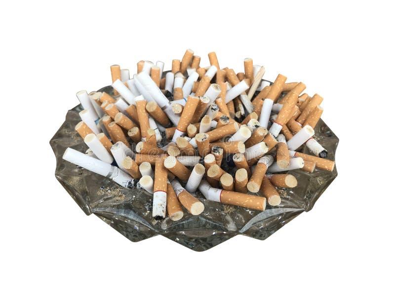 Vele sigaret die die een glasasbakje overlopen op witte achtergrond het knippen weg wordt geïsoleerd omvat stock afbeeldingen