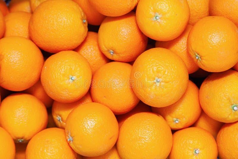 Vele smakelijke rijpe oranje mandarins worden opgestapeld op teller bij de landbouwersmarkt Het concept van het nieuwjaarfruit, v stock foto's
