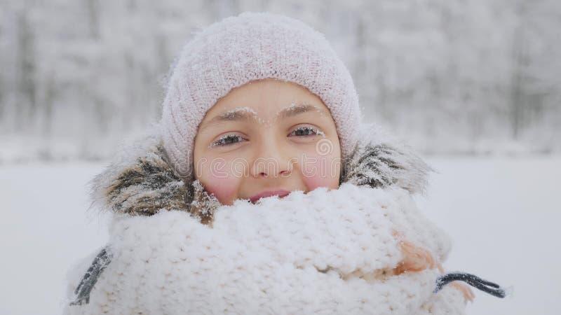Vele sneeuwvlokken vallen op het gezicht van een glimlachend meisje in de wintertijd royalty-vrije stock fotografie