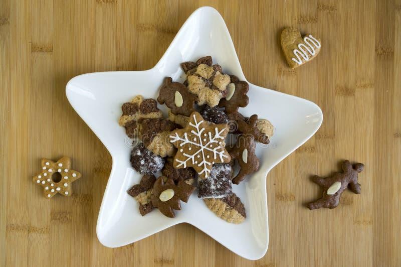 Vele soorten Kerstmiskoekjes op witte plaat, donker en lichte peperkoek, de schotel van de stervorm stock afbeeldingen
