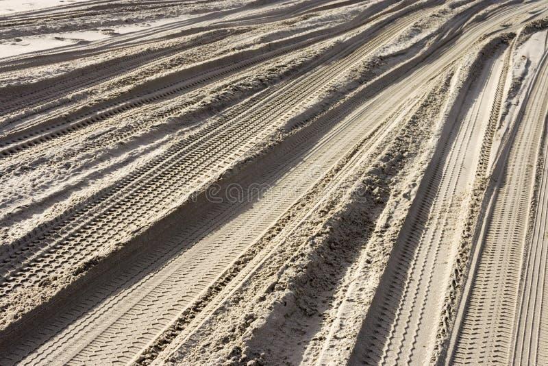 Vele sporen van het loopvlak van banden op het zand op het strand stock foto