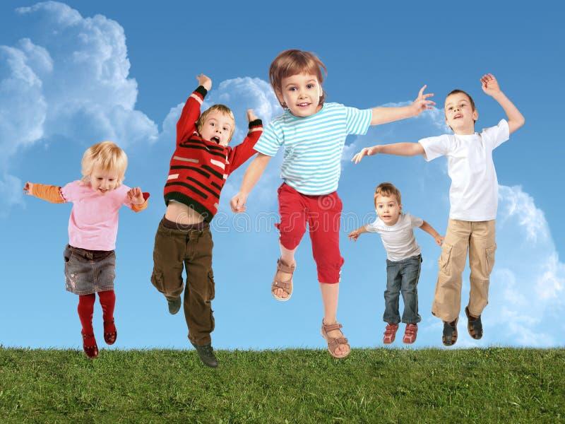 Vele springende kinderen op gras, collage stock afbeeldingen