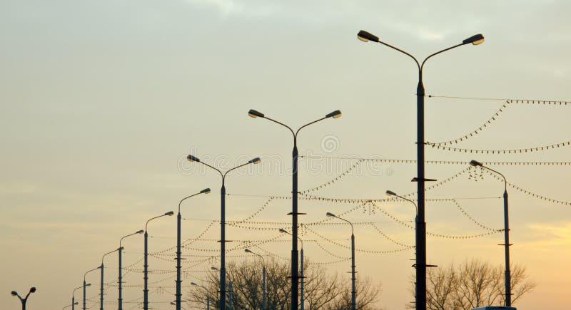 Vele straatlantaarns langs de weg stock afbeelding