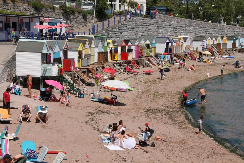 Vele toeristen op het strand en strandhutten in verschillende kleuren in de stad Torquay stock afbeelding