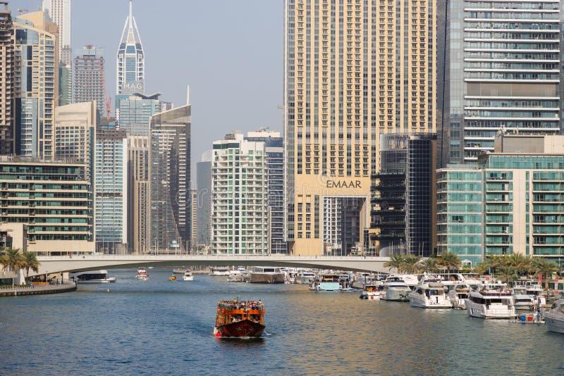 Vele turistiche di legno della nave sulla baia contro lo sfondo delle costruzioni moderne nel distretto del porticciolo del Dubai immagine stock libera da diritti