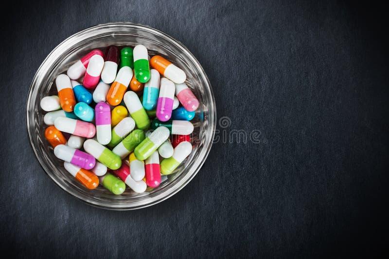 Vele verschillende gekleurde pillen op een zwarte royalty-vrije stock foto
