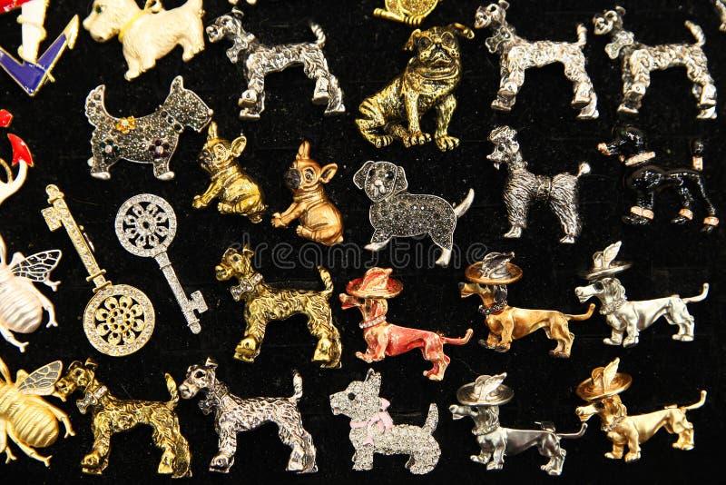 Vele verschillende juwelenbroches in de vorm van honden stock foto