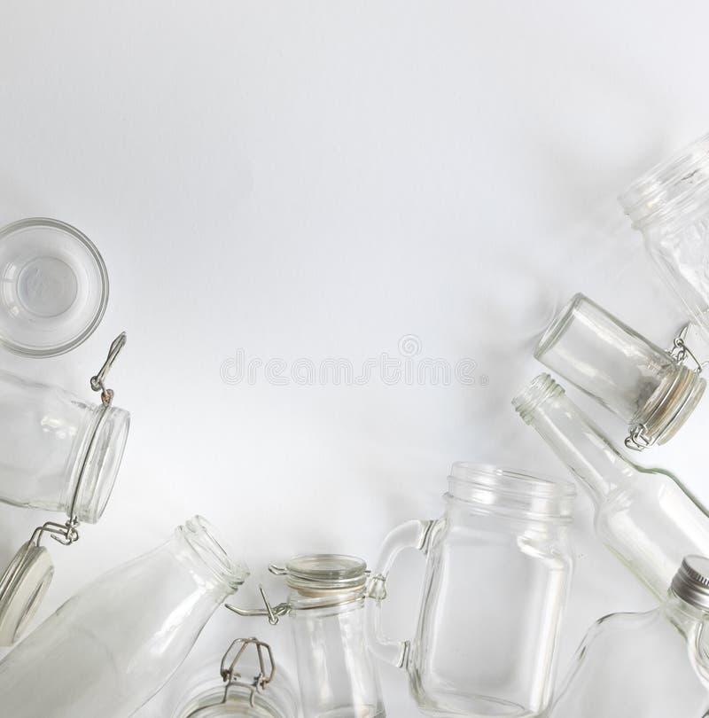 Vele verschillende lege glasflessen die op een witte die achtergrond liggen, hierboven wordt gefotografeerd van royalty-vrije stock afbeelding