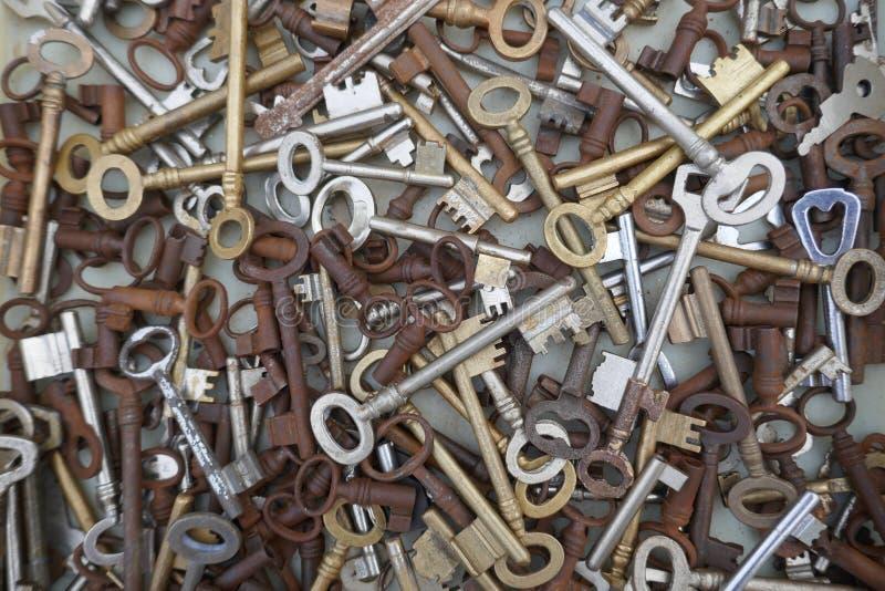 Vele verschillende oude, roestige sleutels bij de vlooienmarkt te verkopen Sluit omhoog, achtergrond en textuur royalty-vrije stock foto