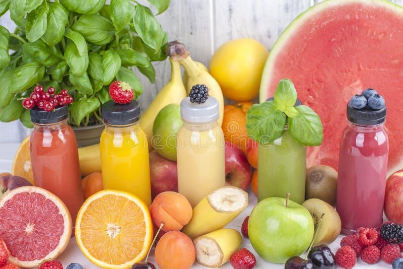 Vele verschillende vruchten en bessen, sap in flessen Vitaminen en gezond voedsel de zomerproducten De ruimte van het exemplaar stock foto's