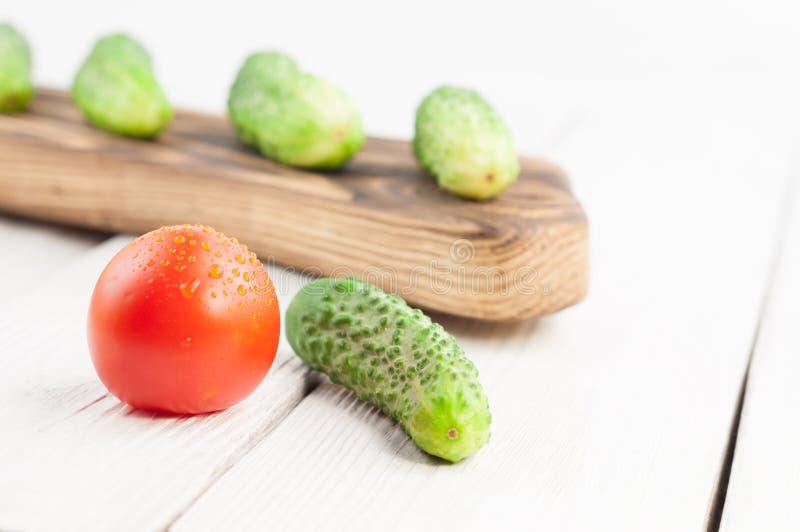 Vele verse groene komkommers op rustieke scherpe raad en één enkele komkommer en rode rijpe tomaat op oude houten planken royalty-vrije stock fotografie