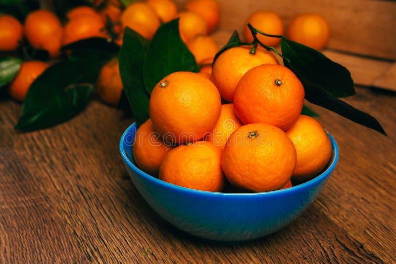 Vele verse mandarijntjes in blauwe kom, die zich op een houten lijst bevinden stock fotografie