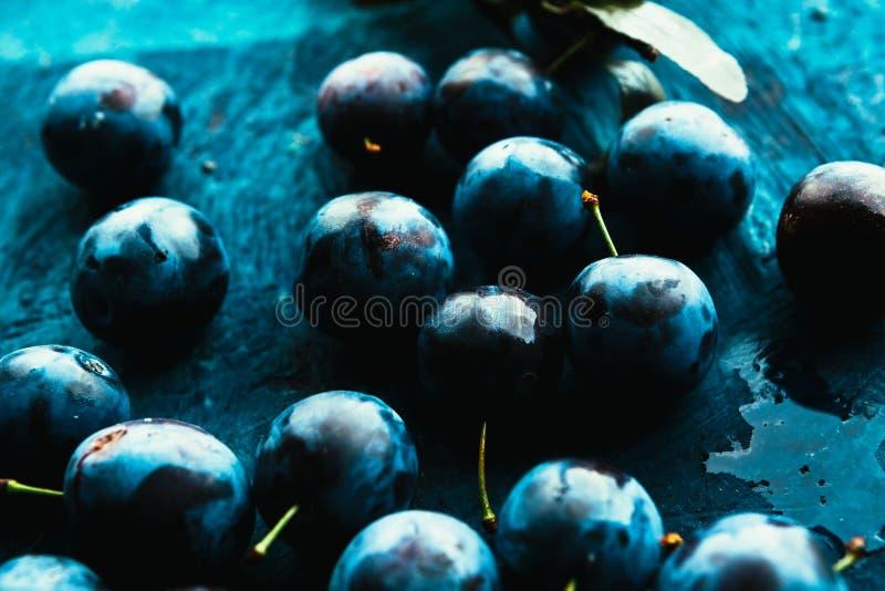 Vele verse pruimen op blauwe achtergrond sluiten omhoog royalty-vrije stock foto's