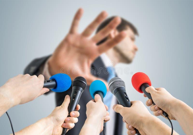 Vele verslaggevers registreren met microfoons een politicus die geen commentaargebaar toont royalty-vrije stock afbeeldingen