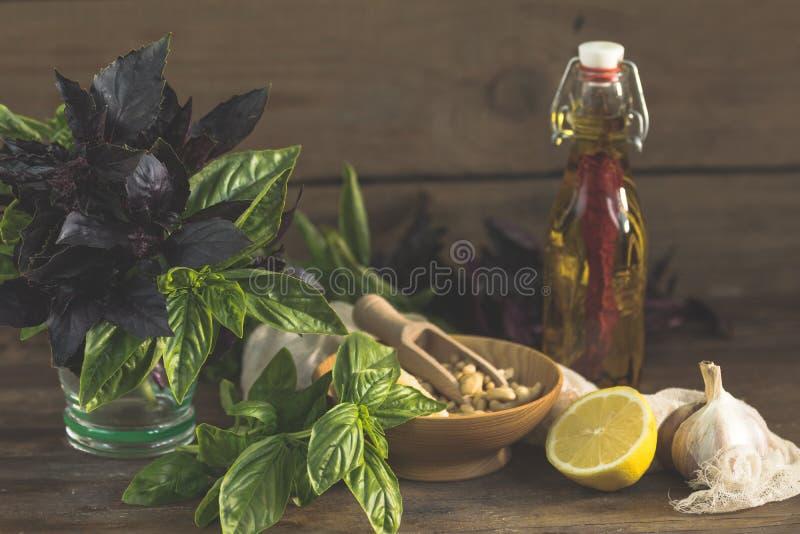 Vele voedselingrediënten voor het maken van pesto op donkere houten achtergrond stock afbeelding
