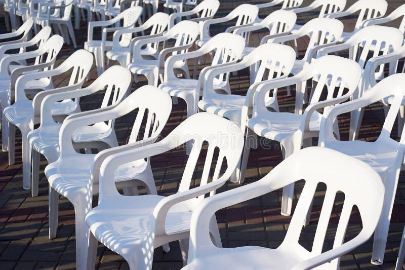 Vele witte plastic stoelen, die op een Zonnige dag, voor de gebeurtenis in openlucht worden blootgesteld royalty-vrije stock fotografie