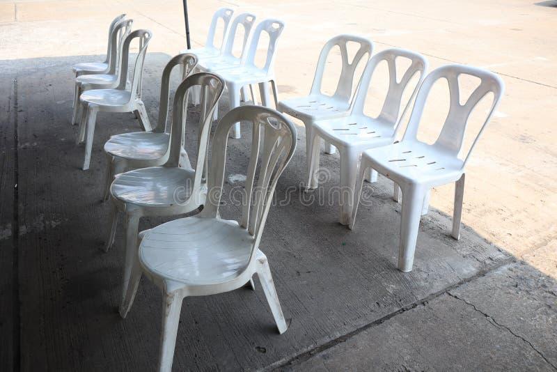 Vele witte plastic stoelen worden samen geschikt stock afbeeldingen